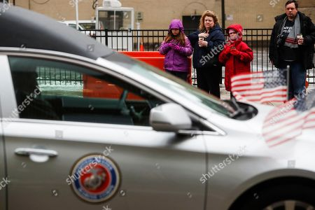 Pedestrians watch a hearse carrying the casket of John H Glenn during his funeral procession down High Street, in Columbus, Ohio. The famed astronaut died Dec. 8 at age 95