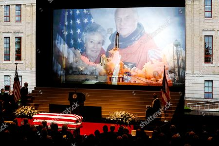 Stock Photo of The casket of John H Glenn rests below an image of Glenn and his wife, Annie, and the launch of the STS-95 space shuttle launch during his funeral ceremony at The Ohio State University, in Columbus, Ohio. Glenn, the famed astronaut, died Dec. 8 at age 95