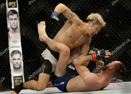 Mizuto Hirota, top, from Japan, punches Cole Miller during the second round of a UFC Fight Night mixed martial arts bout in Sacramento, Calif., . Hirota won by unanimous decision