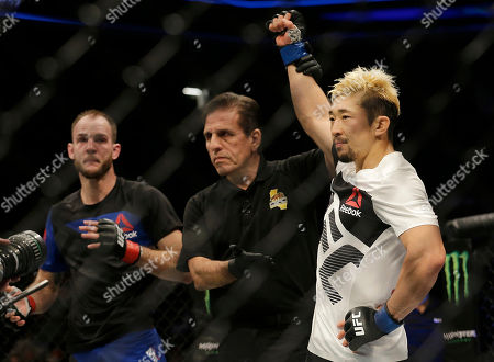 Mizuto Hirota, from Japan, right, has his arm raised after beating Cole Miller, left, in a UFC Fight Night mixed martial arts fight in Sacramento, Calif., . Hirota won by unanimous decision