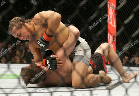 Urijah Faber, top, punches Brad Pickett during the first round of a UFC Fight Night mixed martial arts bout in Sacramento, Calif., . Faber won by unanimous decision