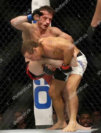 Urijah Faber, bottom, takes down Brad Pickett during the second round of a UFC Fight Night mixed martial arts bout in Sacramento, Calif., . Faber won by unanimous decision