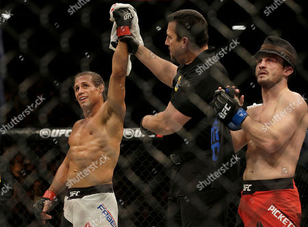 Urijah Faber, left, has his arm raised after beating Brad Pickett, right, by unanimous decision in a UFC Fight Night mixed martial arts fight in Sacramento, Calif