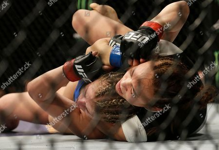 Michelle Waterson, right, applies a choke hold to Paige VanZant during the first round of a UFC Fight Night mixed martial arts fight in Sacramento, Calif., . Waterson won by submission in the first round