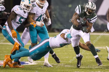 New York Jets running back Matt Forte (22) runs with he ball as Miami Dolphins linebacker Spencer Paysinger (42) dives for him during the NFL game between the Miami Dolphins and the New York Jets at MetLife Stadium in East Rutherford, New Jersey. The Miami Dolphins won 34-13