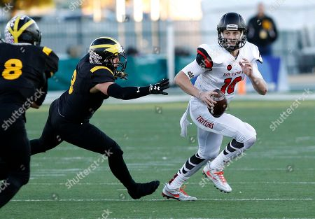 Stock Photo of Andrew Birch, Jack Sears San Clemente quarterback Jack Sears, right, eludes the grasp of Del Oro linebacker Andrew Birch, left, during the first half of the Division 1A high school football championship game, in Sacramento, Calif