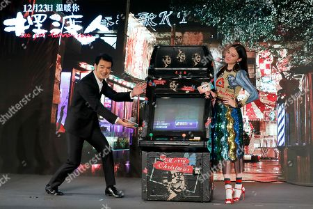 """Takeshi Kaneshiro, Sandrine Pinna Taiwanese-Japanese actor Takeshi Kaneshiro, left, and Taiwanese actress Sandrine Pinna pose with a video game console during a press conference to promote their latest movie """"See You Tomorrow"""" in Beijing, . The movie will open in China on Dec. 23"""