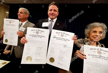 Arizona Electoral College members, from left, Bruce Ash, Robert Graham and Carol Joyce, display their ballots for president-elect Donald Trump at the Capitol in Phoenix, . All 11 Arizona members cast their vote for Trump