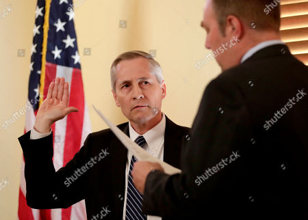 Stock Picture of Newly-appointed Arizona Supreme Court justice Andrew Gould is sworn in by assistant Arizona Secretary of State Lee Miller, right, at the Capitol in Phoenix