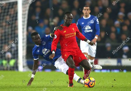 Everton's Idrissa Gana Gueye, left, competes for the ball with Liverpool's Steven Caulker during the English Premier League soccer match between Everton and Liverpool at Goodison Park stadium in Liverpool, England