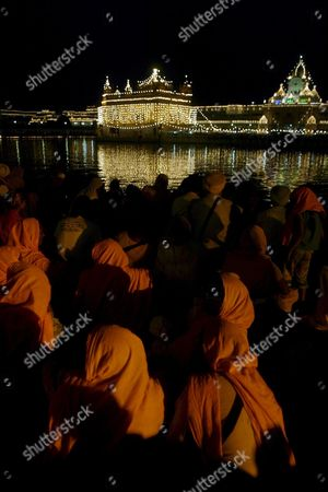 Sikh Women Devotees Wearing Saffron Colour Clothes As Representation of Sikhism Sit at the Golden Temple Premises to Mark the Birth Anniversary of the Fourth Guru Or the Master of the Sikhs Sri Guru Ramdas Ji in Amritsar City India 09 October 2008 the 474th Birth Anniversary of the Fourth Guru Or the Master of the Sikhs Sri Guru Ramdas Ji Who Also Established the City of Amritsar Was Celebrated