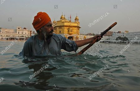 Stock Photo of A Sikh Man Performs the Early Morning 'Sewa' Or the Religious Service by Cleaning the Holy Pond of the Golden Temple On the Occasion of the Birth Anniversary of the Fifth Master Or 'Guru' of the Sikhs Guru Arjan Dev Ji in Amritsar City Punjab India On 02 May 2007 Guru Arjan Dev Ji Compiled and Installed For the First Time the Sri Guru Granth Sahib Ji the Holy Book of Sikh Religion Including Over 2 000 Hymns by Him
