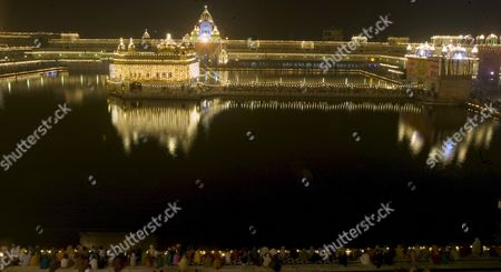 Devotees Sit Along the Holy Pond of the Illuminated Golden Temple the Most Sacred Place For Sikhs All Over the World As They Visit to Pay Obeisance On the Occasion of the Birth Anniversary of the First Sikh Guru Or Master Sri Guru Nanak Dev Ji in the Northern Indian City of Amritsar 13 November 2008 Guru Nanak Dev Ji is the Founder of Sikhism and the First of the Ten Gurus of the Sikhs