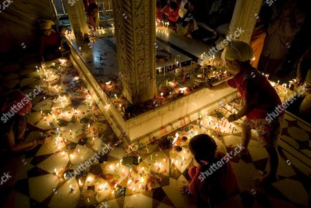 Stock Image of Children Light Candles at Golden Temple the Most Sacred Place For Sikhs All Over the World As They Visit to Pay Obeisance On the Occasion of the Birth Anniversary of the First Sikh Guru Or Master Sri Guru Nanak Dev Ji in the Northern Indian City of Amritsar 13 November 2008 Guru Nanak Dev Ji is the Founder of Sikhism and the First of the Ten Gurus of the Sikhs
