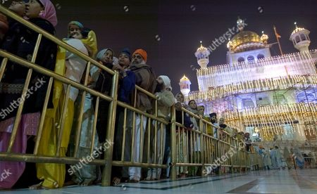 Sikh Devotees Throng to Pay Obeisance in the Pre Dawn Hours at the Golden Temple the Most Sacred Place For Sikhs All Over the World On the Occasion of the Birth Anniversary of the First Sikh Guru Or Master Sri Guru Nanak Dev Ji in the Northern Indian City of Amritsar 13 November 2008 Guru Nanak Dev Ji is the Founder of Sikhism and the First of the Ten Gurus of the Sikhs