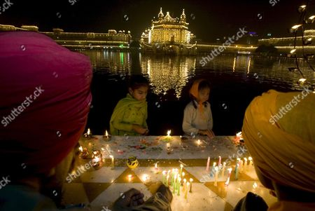 Children Light Candles with the Illuminated Golden Temple the Most Sacred Place For Sikhs All Over the World in the Backdrop As They Visit to Pay Obeisance On the Occasion of the Birth Anniversary of the First Sikh Guru Or Master Sri Guru Nanak Dev Ji in the Northern Indian City of Amritsar 13 November 2008 Guru Nanak Dev Ji is the Founder of Sikhism and the First of the Ten Gurus of the Sikhs