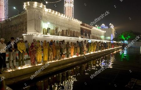 Stock Picture of Devotees Stand For the Evening Prayer Facing the Illuminated Golden Temple (not Pictured) the Most Sacred Place For Sikhs All Over the World As They Visit to Pay Obeisance On the Occasion of the Birth Anniversary of the First Sikh Guru Or Master Sri Guru Nanak Dev Ji in the Northern Indian City of Amritsar 13 November 2008 Guru Nanak Dev Ji is the Founder of Sikhism and the First of the Ten Gurus of the Sikhs