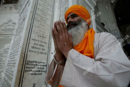 A Sikh Devotee Pays Obeisance Facing the Golden Temple (not Pictured) the Most Sacred Place For Sikhs All Over the World On the Occasion of the Birth Anniversary of the First Sikh Guru Or Master Sri Guru Nanak Dev Ji in the Northern Indian City of Amritsar 13 November 2008 Guru Nanak Dev Ji is the Founder of Sikhism and the First of the Ten Gurus of the Sikhs