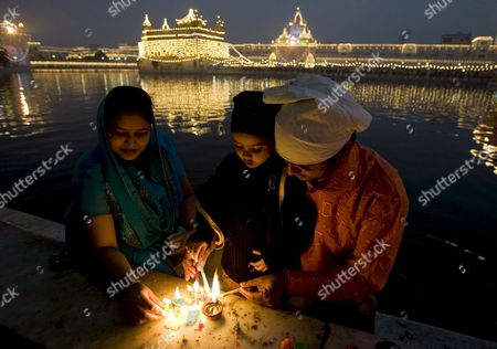 A Family Lights Candles and Lamps Along the Holy Pond of the Illuminated Golden Temple the Most Sacred Place For Sikhs All Over the World As They Visit to Pay Obeisance On the Occasion of the Birth Anniversary of the First Sikh Guru Or Master Sri Guru Nanak Dev Ji in the Northern Indian City of Amritsar 13 November 2008 Guru Nanak Dev Ji is the Founder of Sikhism and the First of the Ten Gurus of the Sikhs