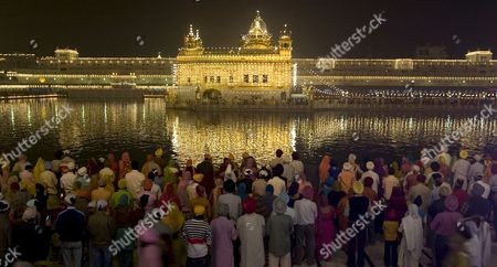 Devotees Stand For the Evening Prayer in Front of the Illuminated Golden Temple the Most Sacred Place For Sikhs All Over the World As They Visit to Pay Obeisance On the Occasion of the Birth Anniversary of the First Sikh Guru Or Master Sri Guru Nanak Dev Ji in the Northern Indian City of Amritsar 13 November 2008 Guru Nanak Dev Ji is the Founder of Sikhism and the First of the Ten Gurus of the Sikhs