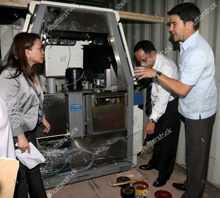 Stock Image of Optical Media Board (omb) Chair Eduardo Manzano (r) and Bureau of Customs (boc) Commissioner Napoleon Morales (2-r) Inspect Machines Used For Replicating Optical Media Such As Cd's and Dvd's in Manila Philippines 26 May 2009 Authorities Intercepted Shipments of Replicating Machines and Accessories From Hong Kong Estimated to Be Worth 300-million Pesos (4 5-million Euro) Following Alerts That These Could Be Used For Optical Media Piracy Operations