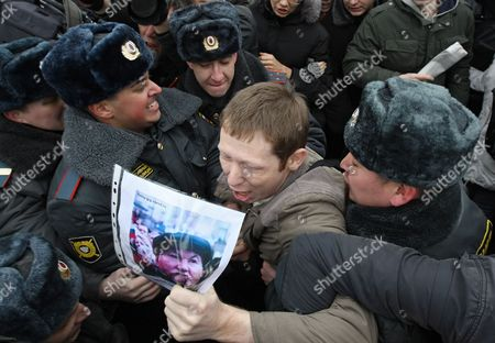 Police Officers Scuffle with a Protester Holding a Portrait of Moscow Mayor Yury Luzhkov (c) During an Opposition Rally in Moscow Russia 20 March 2010 According to Local Media Reports Thousands of People Throughout Russia Protested Against Prime Minister Putin's Government and the Fall of Living Standards Since the Economic Crisis Some 50 Rallies Were Thus Organized by a Coalition of Opposition Groups Which Declared a National 'Day of Anger' on 20 March Moscow Protesters Demanded the Discharge of Moscow Mayor Yury Luzhkov They Shouted the Slogans: 'Moscow Without Luzhkov' 'Russia Without Putin' Russian Federation Moscow