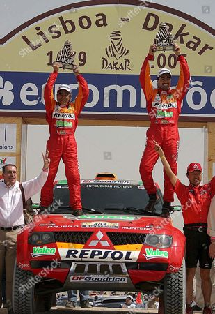 Driver Luc Alphand (r) and Navigator Gilles Picard (l) From France Celebrate Their Victory First Place in the Car Category of the 2006 Dakar Rally On the Podium at Lac Rose Senegal Sunday 15 January 2006 Alphand Led Heading Into the Final Stage Which Race Organizers Said Would not Be Timed to Honor Two Boys Killed During the Race