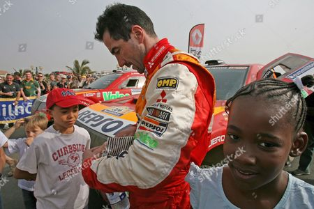 Driver Luc Alphand From France (c) Signs Autographs For Children After Reaching Dakar Senegal Saturday 20 January 2007 Driver Alphand and Navigator Gilles Picard Are in Second Place Overall Going Into Sundays Final Stage of the Race