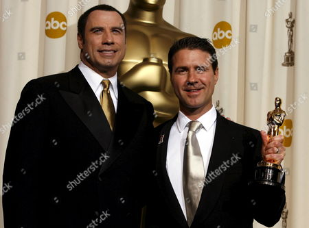 Stock Image of Dion Beebe (r) Poses with Presenter John Travlota (l) As He Holds Up His Oscar For 'Achievement in Cinematography' For the Film 'Memoirs of a Geisha' at the 78th Annual Academy Awards in Hollywood California Sunday 05 March 2006