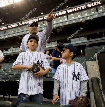 Henry Garza (rear) Stands with His Son Ricky Garza (l) and Stepson Damien Marquez (r) As They Try to Get the Attention of New York Yankee Players During Warmups Before the Start of Their Major League Baseball Game Against the Chicago White Sox at U S Cellular Field in Chicago Illinois Usa 22 April 2008