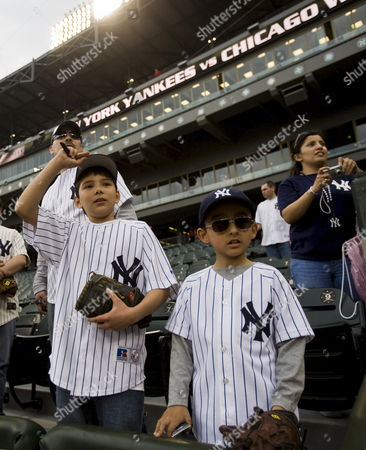 Henry Garza (rear) Stands with His Son Ricky Garza (l) and Stepson Damien Marquez (r) As They Try to Get the Attention of New York Yankee Players During Warmups Before the Start of Their Major League Baseball Game Against the Chicago White Sox at U S Cellular Field in Chicago Illinois Usa 22 April 2008 United States Chicago