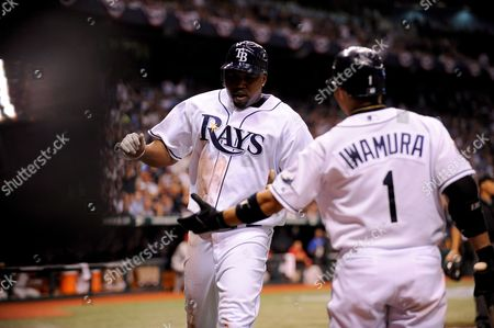 Tampa Bay Rays Cliff Floyd (l) is Greeted by Teammate Akinori Iwarmura of Japan After Scoring Against the Philadelphia Phillies in the Fourth Inning of Game Two of the World Series at Tropicana Field in St Petersburg Florida Usa 23 October 2008
