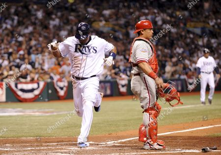 Tampa Bay Rays Cliff Floyd (l) Scores As Philadelphia Phillies Catcher Carlos Ruiz Looks On in the Fourth Inning of Game Two of the World Series at Tropicana Field in St Petersburg Florida Usa 23 October 2008