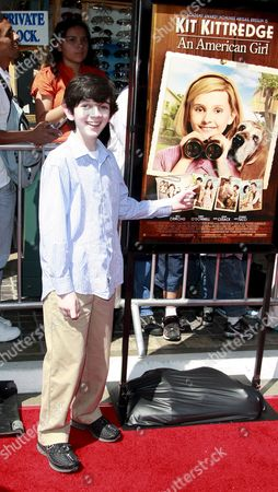 Us Actor Zach Mills Points at His Photo in the Poster As He Arrives at the World Premiere of 'Kit Kittredge: an American Girl' at the Grove in Los Angeles California Usa On 14 June 2008 the Film is Based On the American Girl Doll Line and Centers On Kit Kittredge a Young Woman Who Grows Up in the Early Years of the Great Depression