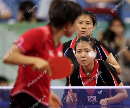 Japan's Sayaka Haruna Fukuoka Serves the Ball Over Korea's Park Mi Young and Kim Kyung Ah (facing the Camera) During Women's Table Tennis Team Bronze Medal Event During the Beijing 2008 Olympic Games at the Peking University Gymnasium Beijing China 17 August 2008 Korea Leading Against Japan 2-0