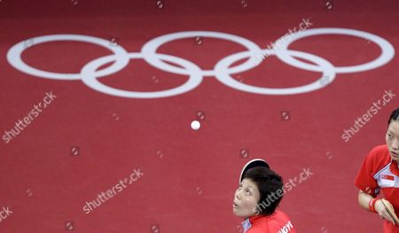 Singapore's Yue Gu Wang Next to Jia Wei Li Serves the Ball Over Korea's (unseen) Mi Young Park and Kyung Ah Kim During the Semifinal Round 2 in the Women's Team Table Tennis Event During the Beijing 2008 Olympic Games at the Peking University Gymnasium Beijing China 15 August 2008
