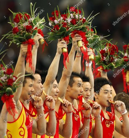 (l-r) China's Chen Yibing Huang Xu Li Xiaopeng Xiao Qin Yang Wei Zou Kai Bite Their Gold Medals at the Medal Ceremony of the Artistic Gymnastics Men's Team During the Olympic Games in Beijing China 12 August 2008 the Chinese Won the Gold Medal For the Event with Japan and United States Taking Silver and Bronze Respectively