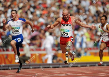 Canada's Earle Connor (r) Crosses the Finish Line Ahead of Great Britain's John Mcfall (l) During the Men's 100m - T42 Final at the Beijing 2008 Paralympic Games China 14 September 2008 Connor Won the Race with a New Paralympic Record of 12 32 Seconds Popow Heinrich of Germany (not Pictured) Came in Second Place and Mcfall in Third