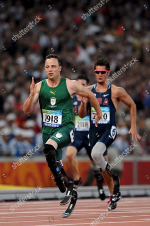 Oscar Pistorius (l) of South Africa Crosses the Finish Line Ahead of Jim Bob Bizzell (r) of the Usa During the Men's 200m - T43 Final at the National Stadium Also Known As the 'Birds' Nest' During the Beijing 2008 Paralympic Games China 13 September 2008 Pistorius Won with a New Paralympic Record Time of 21 67 Seconds Bizzell Came in Second Followed by Ian Jones of Great Britain in Third