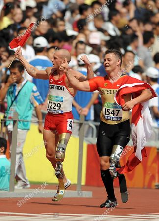 Canada's Earle Connor (l) and Germany's Heinrich Popow (r) Celebrate at the End of the Men's 100m - T42 Final at the Beijing 2008 Paralympic Games China 14 September 2008 Connor Won the Race with a New Paralympic Record of 12 32 Seconds Ahead of Popow Who Finished Second with John Mcfall of Great Britain in Third