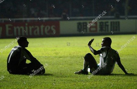 Saudi Arabia's Yasser Al Mosailem (l) Chats with Osama Hawsawi (r) As They Wait For Stadium Lights to Go On During Their Match Against Korea at the Afc Asian Cup Soccer Championships at Bung Karno Stadium in Jakarta On 11 July 2007 Saudi Arabia and Korea Played 1-1