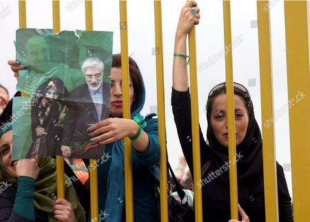 Supporters of Iranian Presidential Candidate Mir-hossein Moussavi Hold a Poster Depicting Him and His Wife Zahra Rahnavard During an Election Campaign Rally at the Enqelab Stadium in the City of Karaj West of the Capital Tehran Iran On 06 June 2009 Moussavi Could not Hold His Speech in the City of Karaj Because of a Sudden Failure of the Audio System Moussavi Was Scheduled to Hold a Speech in Karajs Enqelab Stadium Which Was Packed with Tens of Thousands of His Supporters But Just Before the Speech Was Supposed to Start the Audio System Suddenly Collapsed