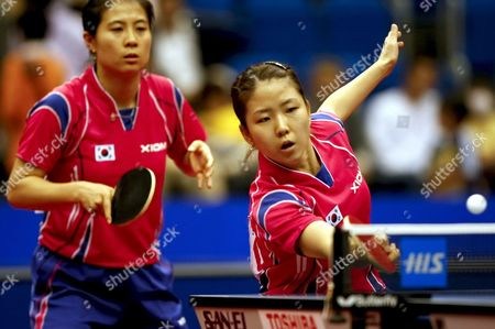 Stock Picture of Park Mi Young (r) of South Korea Hits a Forehand Return As Her Partner Kim Kyung Ah (l) Looks On During Their Women's Doubles Semi Final Match Against China's Ding Ning and Guo Yan at the World Table Tennis Championships in Yokohama South of Tokyo Japan 04 May 2009