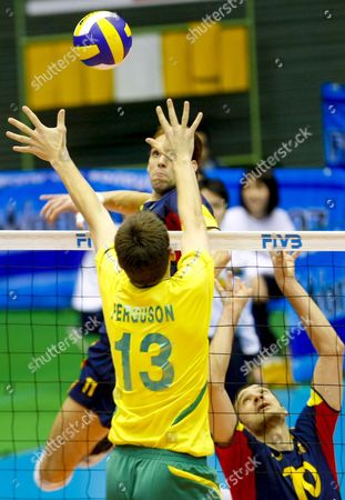 Spanish Setter Miguel Angel Falasca (r) Tosses the Ball and His Teammate Javier Subiela (facing L) Jumps to Spike It While Australia's David Ferguson (l) Tries to Block It During the 4th Round Match of the 2007 Fivb Men's World Cup Volleyball Held at Metropolitan Komazawa Olympic Park in Tokyo Japan 30 November 2007 Spain Beat Australia 3-0 (21-25 19-25 20-25)
