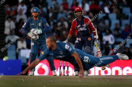 Delhi Daredevils Batsman Tillakaratne Dilshan (back R) Watches with Deccan Chargers Captain and Wicketkeeper Adam Gilchrist (back L) As Bowler Andrew Symonds (front) Attempts to Field His Shot in the 2009 Ipl T20 Semi-final Cricket Match Between the Delhi Daredevils and the Deccan Chargers Played at Supersport Park in Centurion North of Johannesburg South Africa 22 May 2009