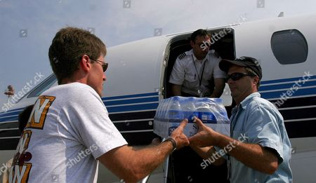 (left to Right) Northrop Grumman Employees Paul Finch Joe Miller and Mark Isham Unload Supplies From a Jet at the Trent Lott International Airport in Pascagoula Miss On Friday 2 September 2005 the Company is Trying to Get Supplies to Their Shipyard and Employees in the Area After Hurricane Katrina Devastated the Area