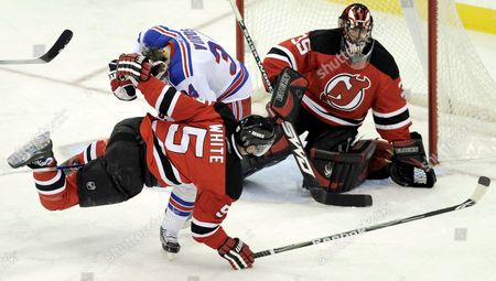 The Devils' Colin White (2nd L) is Tripped by the Rangers' Aaron Voros (l) As the Teammate Scott Clemmensen (r) Looks On During the First Period of the Game Between the New York Rangers and the New Jersey Devils at the Prudential Center in Newark New Jersey Usa 12 December 2008