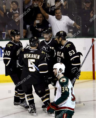 Minnesota Wild Player Aaron Voros (front) Skates Past Dallas Stars Players Celebrates the Goal by Antti Miettinen in the Third Period of Their Nhl Ice Hockey Game at the American Airlines Center in Dallas Texas Usa 7 January 2008