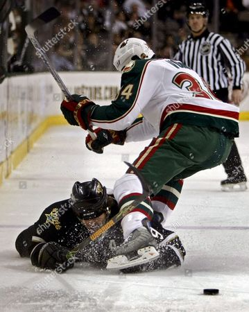Minnesota Wild Player Aaron Voros (r) Trips Up Dallas Stars Player Mike Modano (l) While Going For the Puck in the First Period of Their Nhl Ice Hockey Game at the American Airlines Center in Dallas Texas Usa 7 January 2008