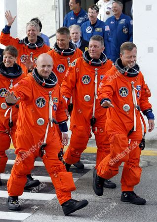 The Sts-121 Nasa Flight Crew Leaving the Operations and Checkout Building (onc) Under Tight Security at Kennedy Space Center (ksc) Cape Canaveral Florida Sunday 02 July 2006 For Launch Pad 39b Astronauts (l-r)pilot Mark E Kelly Commander Steven W Lindsey Mission Specialist Lisa M Nowak Michael E Fossum Piers J Sellers Stephanie D Wilson and European Space Agency (esa) Astronaut Thomas Reiter of Germany Wave Before Entering the Van That Will Transport the Crew to the Launch Pad